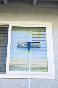 sponge and squeegee on a pole to wash the exterior windows of a home.